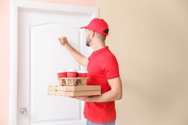 Guapo trabajador de servicio de entrega de alimentos llamando a la puerta