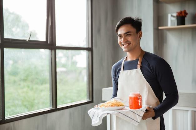 Guapos camareros asiáticos vistiendo delantal sirviendo comida y bebida con sonrisa