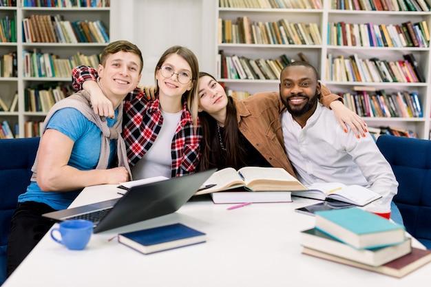 Guapos, sonrientes, felices, amigos de raza mixta, estudiantes, compañeros de trabajo, sentados a la mesa en una biblioteca moderna o en un lugar de coworking y abrazándose, mirando a la cámara