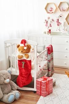 Guardería navideña, sala de juegos para niños decorada para año nuevo, dormitorio infantil blanco, juguetes y regalos navideños en dormitorio infantil, cama blanca con peluches