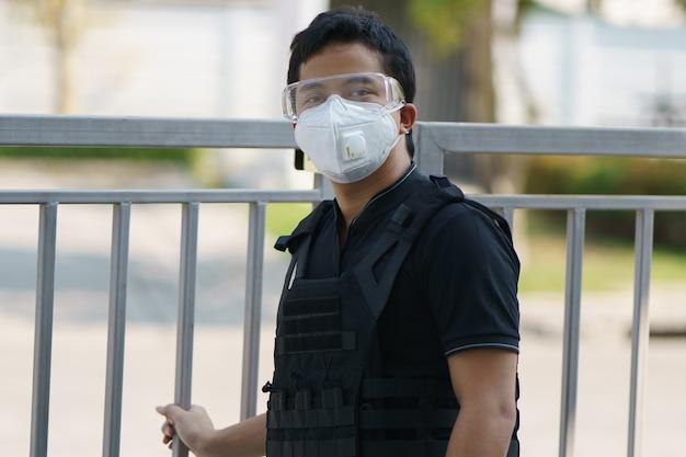 Guardia de seguridad del hombre con mascarilla, gafas y a prueba de balas al aire libre.