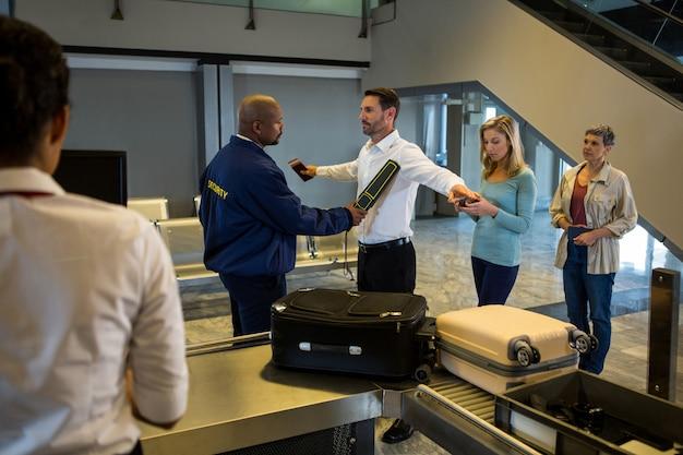 Guardia de seguridad registra a los pasajeros de pie en la cola