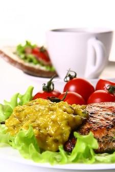 Guarnición de comida con filete y verduras y café.