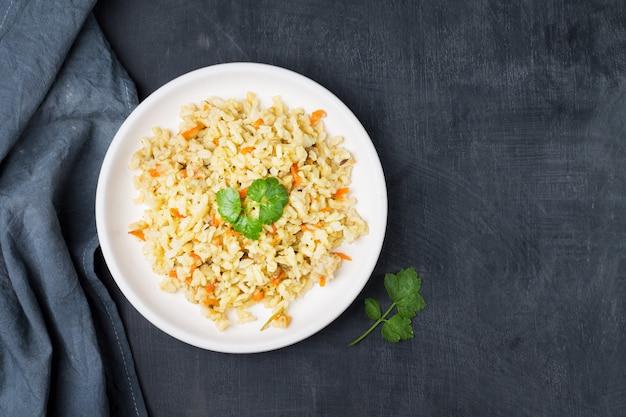 Guarnición guisada de arroz integral con zanahorias y cebollas en un recipiente sobre una servilleta de lino gris.