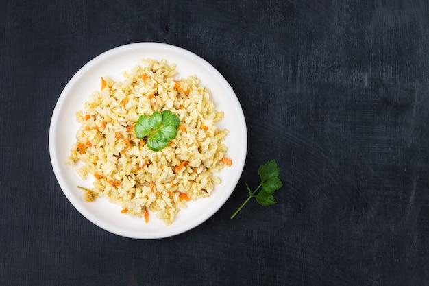 Guarnición vegetariana guisada de arroz integral con cebolla y zanahoria en un plato blanco sobre negro