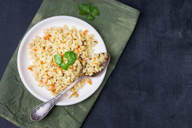 Guarnición vegetariana guisada de arroz integral con cebolla y zanahoria en un recipiente sobre una madera clara
