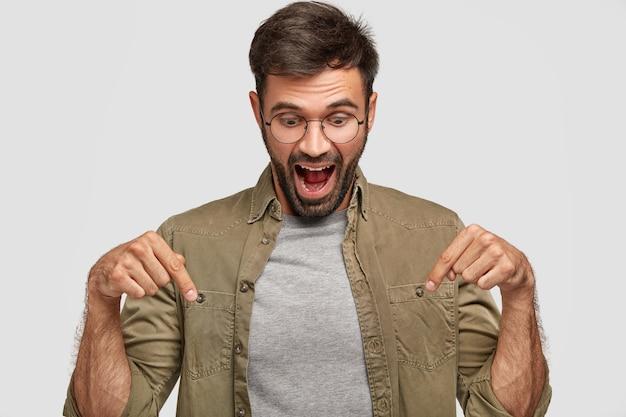 ¡guau, eso es asombroso! el hombre joven sorprendido sorprendido mira con sorpresa hacia abajo, señala con ambos dedos índices, vestido informalmente, abre la boca ampliamente con asombro, aislado sobre una pared blanca