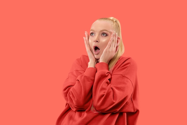 Guau. hermoso retrato frontal de medio cuerpo femenino aislado sobre fondo de estudio de coral. joven mujer emocional sorprendida de pie con la boca abierta. las emociones humanas, el concepto de expresión facial. colores de moda