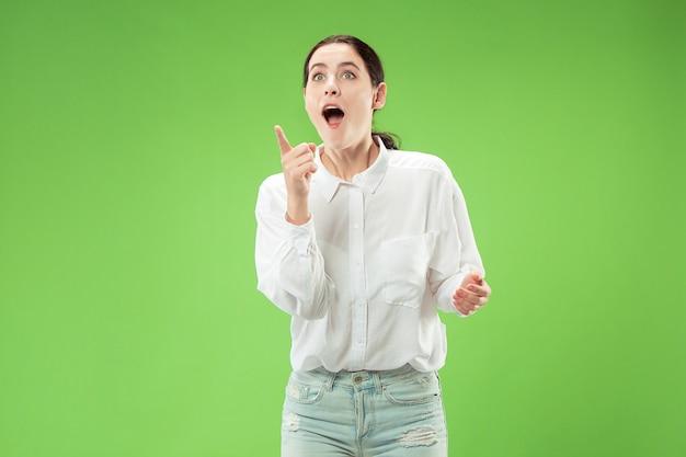 Guau. hermoso retrato frontal de medio cuerpo femenino aislado sobre fondo verde. joven mujer sorprendida emocional de pie con la boca abierta