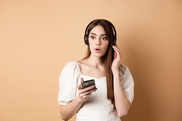 ¡guau melodías increíbles! chica joven emocionada sorprendida con la nueva canción, escuchando música en auriculares y se ve impresionado, sosteniendo el teléfono celular, fondo beige.