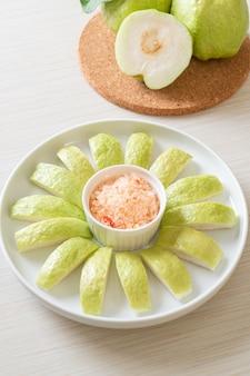 Guayaba fresca en rodajas con salsa de chile y sal