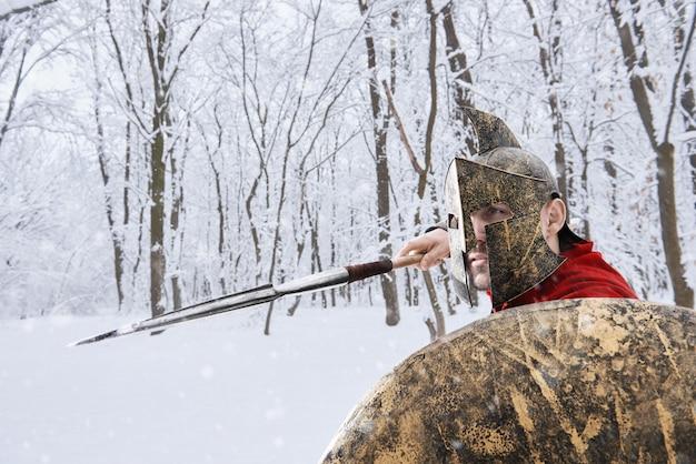 Guerrero espartano está cazando en el bosque de invierno