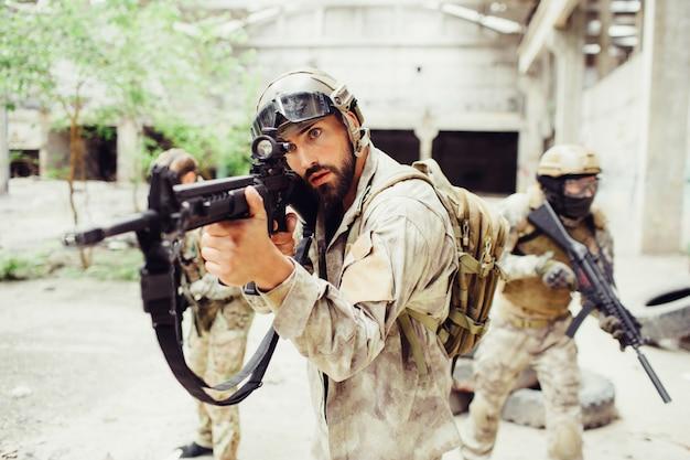 Guerrero está parado afuera y apuntando. él está sosteniendo el rifle en sus manos. otros dos tipos están de pie detrás de él y exploran la territotia.