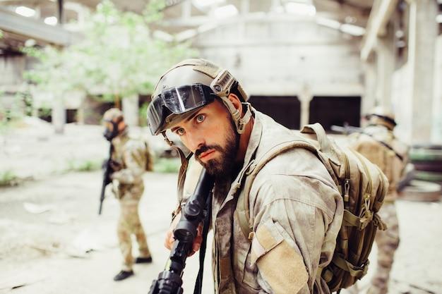 El guerrero serio y concentrado está de pie y mira hacia adelante. él es un rifle negro en sus manos. otros dos hombres están mirando alrededor y revisando el edificio.