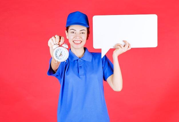 Guía femenina en uniforme azul sosteniendo un tablero de información rectangular blanco con un reloj despertador.