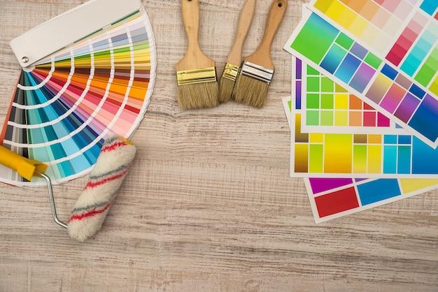 Guía de paleta de colores y rodillo de pincel sobre tablero de madera