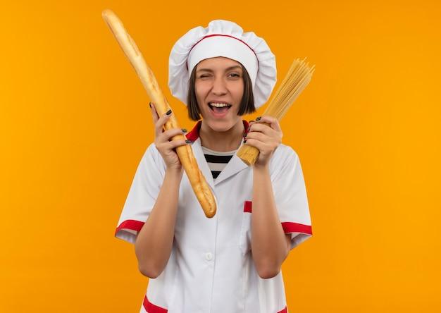 Guiño alegre joven cocinera en uniforme de chef sosteniendo palitos de pan y pasta de espagueti aislado en naranja