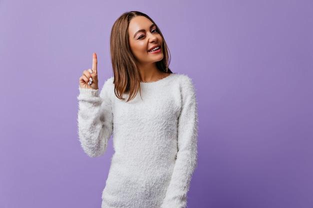 Guiños de niña alegre iniciativa, mostrando que tiene una nueva idea. bonita estudiante feliz de la llegada de musa y posando en una pared púrpura con espacio para texto