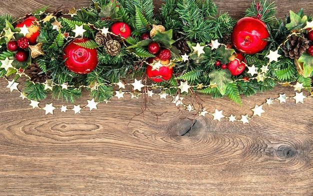 Guirnalda de adornos navideños con manzana roja y ramas de pino verde sobre fondo de madera
