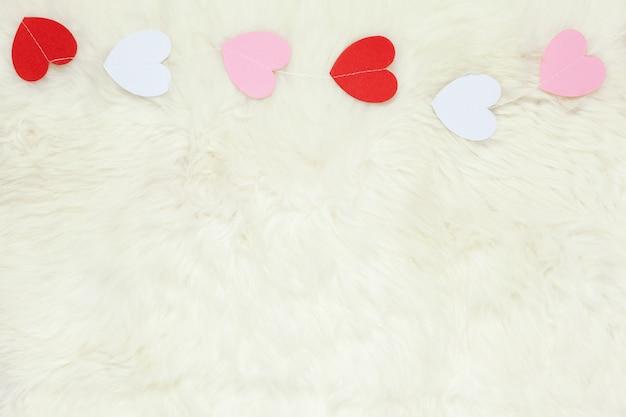 Guirnalda de corazones de papel blanco, rosa y rojo sobre alfombra de piel blanca como la leche de piel de oveja, espacio de copia, plano