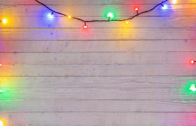 Guirnalda eléctrica con bombillas multicolores sobre una superficie de madera, fondo de navidad y año nuevo