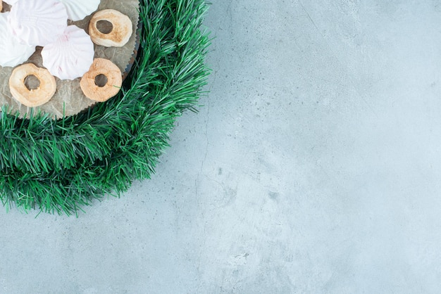 Guirnalda envuelta alrededor de una tabla con galletas y rodajas de manzana secas sobre mármol.