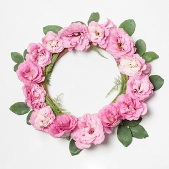 Guirnalda de flores rosas y plantas verdes.