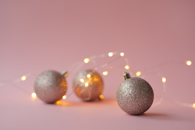 Guirnalda y globos navideños se encuentran sobre un fondo rosa