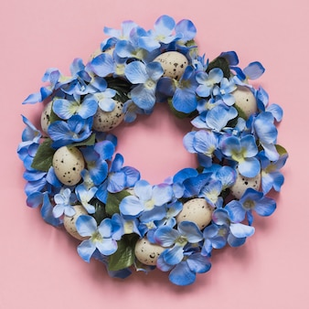 Guirnalda hecha de flores azules y huevos.
