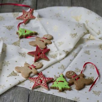 Guirnalda hecha a mano de la navidad con los hombres, el árbol y las estrellas del jengibre en fondo de madera.