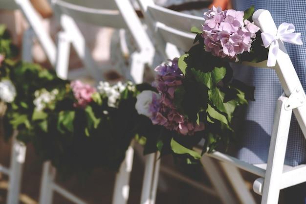Guirnalda de hojas y hortensias moradas en las sillas.