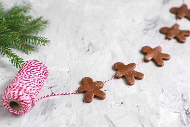 Guirnalda hombre de jengibre hilo rojo abeto masa de brunch concepto de navidad fiesta de año nuevo