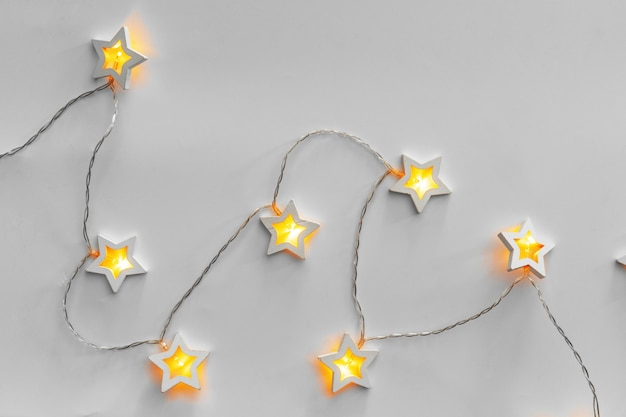 Guirnalda iluminada en forma de estrella sobre fondo gris claro