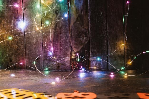 Guirnalda led de color en una pared de madera y calabazas talladas en papel naranja sobre la mesa.