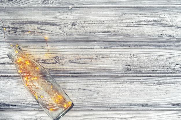 Guirnalda de luces en una botella de vidrio sobre un fondo de madera