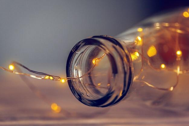 Guirnalda de luces en una botella de vidrio sobre un fondo oscuro