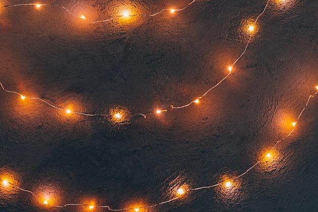 Guirnalda de luz cálida iluminada de cerca sobre fondo oscuro