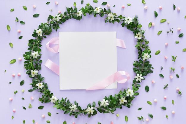 Guirnalda de marco de flores y hojas con tarjeta en blanco