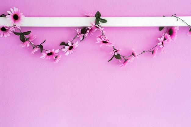Guirnalda de margaritas púrpuras rosas coloridas alegres que cuelgan en la textura de fondo de la pared rosa hermosa