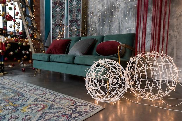 Guirnalda de navidad brillante en forma de bolas cerca de sofá verde en la sala de estar
