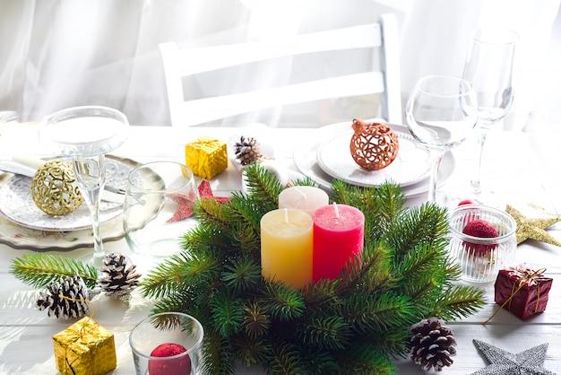 Guirnalda de la navidad con las velas grandes coloridas en una tabla con un ajuste de la tabla de la navidad
