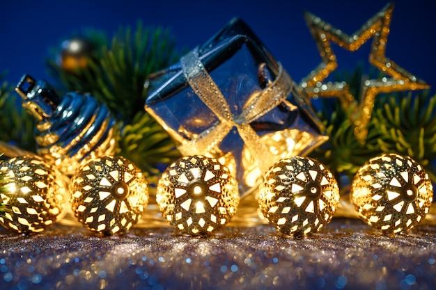 Guirnalda navideña dorada con abeto sobre brillo azul