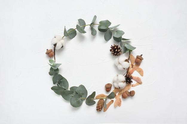 Guirnalda otoño hojas de eucalipto y bellota, marco de cono en blanco