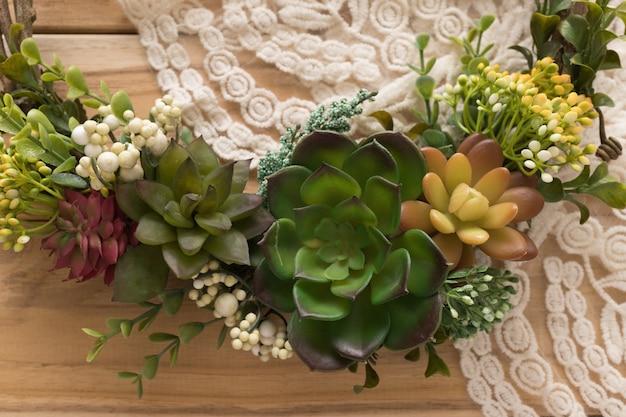 Guirnalda de plantas suculentas con detalle de vestido de novia en superficie de madera