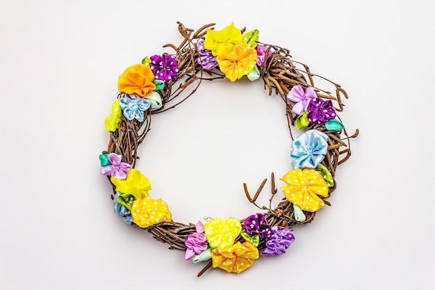 Guirnalda de ramas de abedul y flores coloridas artesanales aisladas sobre fondo blanco. composición de primavera, decoración de pascua. hecho a mano con cintas de lunares satinados, quédate en casa
