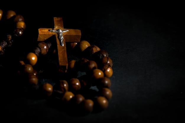 Guirnalda del santo rosario de madera sobre un fondo negro
