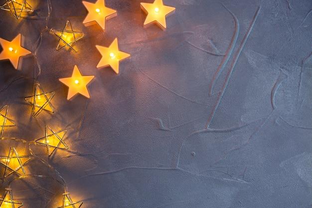 Guirnaldas decorativas de navidad estrellas y velas que brillan intensamente una luz sobre fondo de textura gris. endecha plana