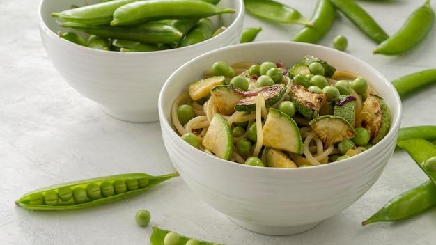 Guisantes de alto ángulo con espaguetis y verduras en un tazón