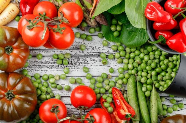 Guisantes esparcidos de un cubo con pimientos, tomates, bok choy, vainas verdes, espárragos, zanahorias en una pared de madera.