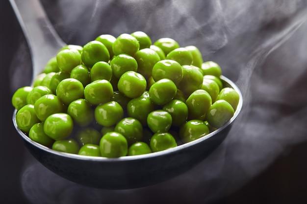 Guisantes verdes en un cucharón con vapor que sale de él contra un fondo oscuro. de cerca